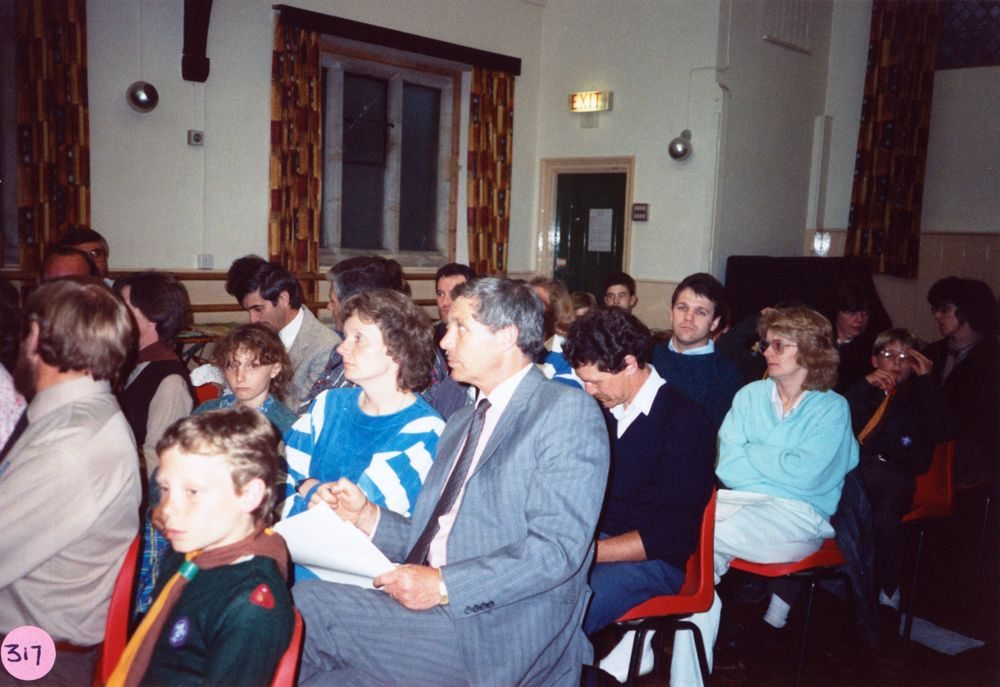 June 1988 Cub/Scout AGM. Front: Bill Edbury (back view), scout, Marianne? Peedell, Malcolm? Peedell, Geoff Divey, ?. Against window: David Monk, David Robey.