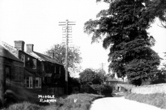 1920s From Enstone Road, looking east to the crossroads. On the south side, the wall and trees have now gone.