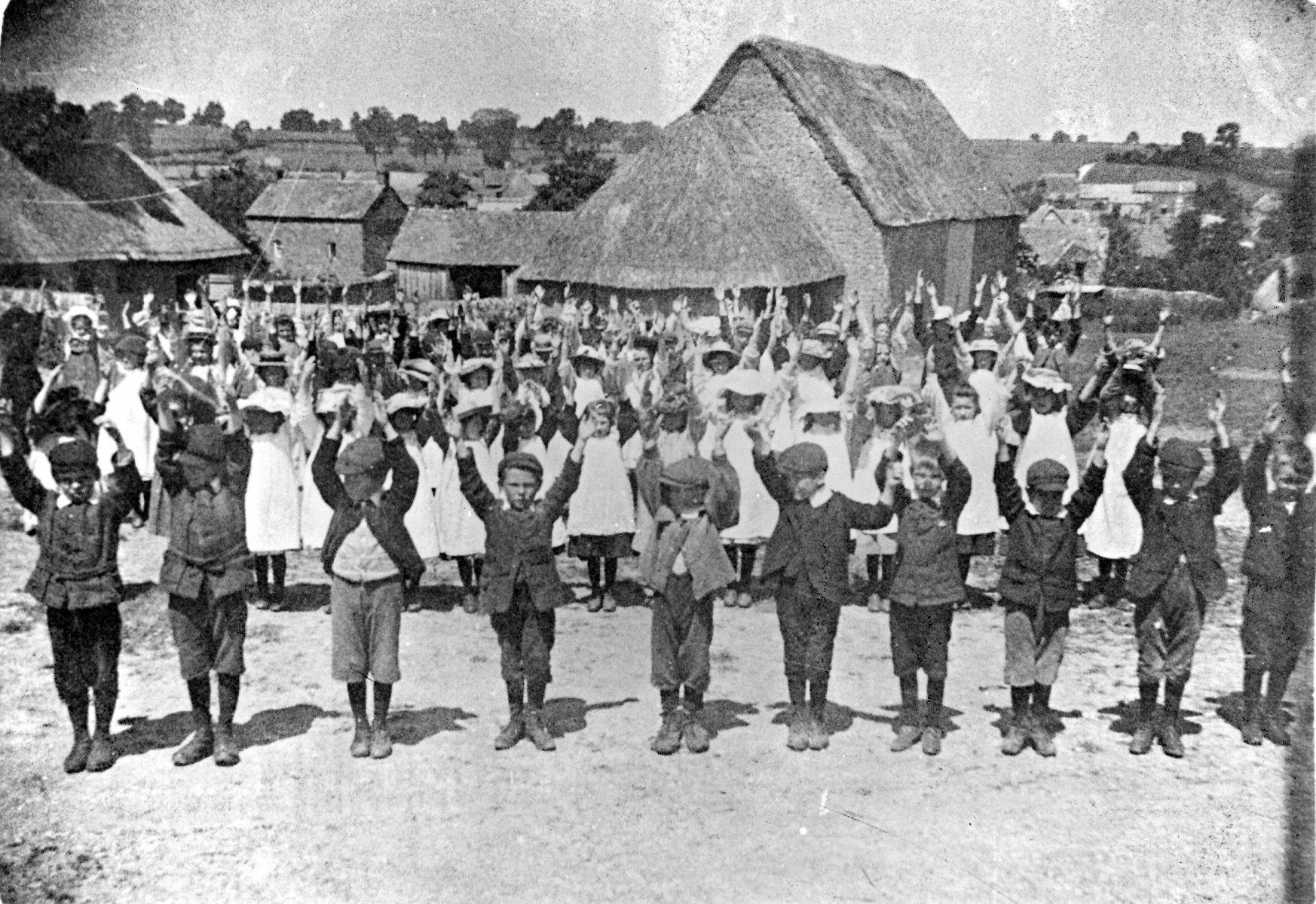 c1905 School children drilling in the school yard. Thatched Village Farm Barn / Langstone House in the background.