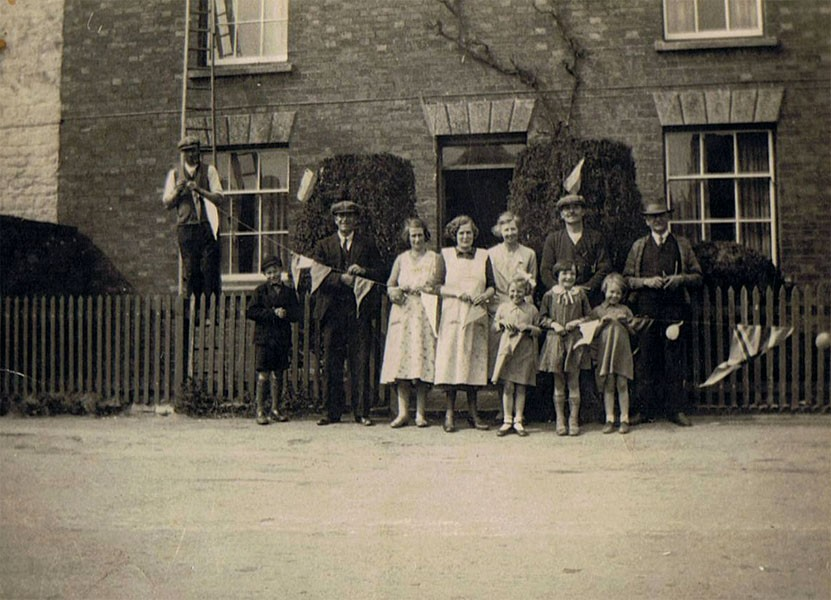 1935 George V Silver Jubilee - Putting up decorations in North Street. Mr. Walter Hazell on the ladder, Victor Hazell (boy). Bill Irons, Florence Hazell, Ethel Jarvis, Rose West, Tom Hazell, Sid Cox (?). Three girls - l to r Diana Jarvis, Violet Hazell, Barbara Jarvis.