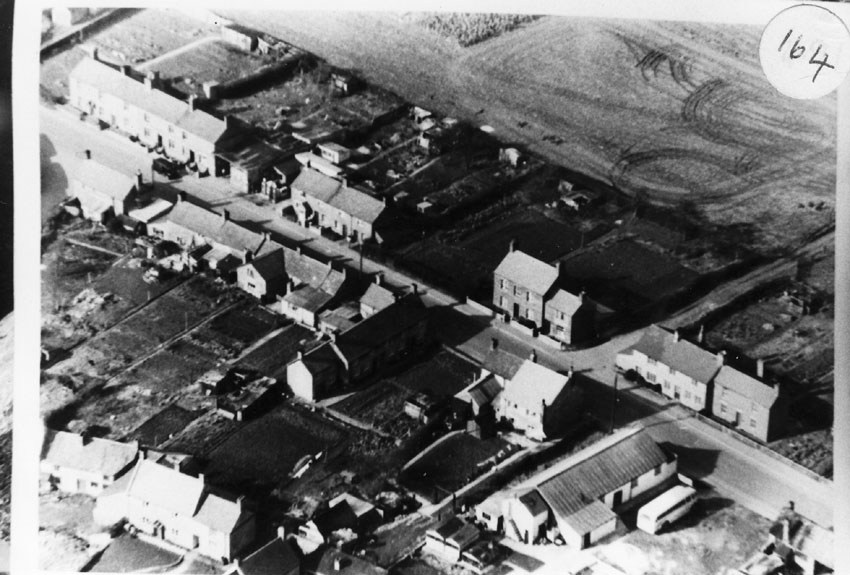 1959. Aerial view of Middle Barton. In the foreground is the cinema with a coach parked beside it.