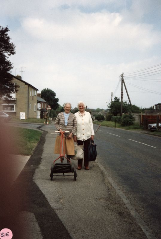 1988 Mrs. Winifred Pritchard and Mrs. Lilian Davis in Enstone Road on their way to Westcote Barton churchyard.