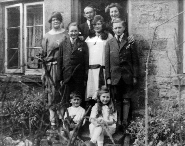Stewart family l -> r in doorway: Solomon and Eliza Stewart; middle row: Edie, Sid, Doll and Bob; front row: William, Muriel.