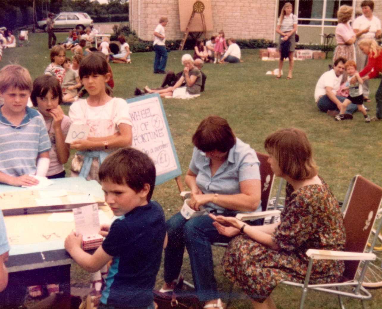 c. 1980 Middle Barton School Fete. Jamie Edbury, Tanya Southam, Tamsin Blencoe, Luke Morgan. Unknown. Teacher sitting on right is Mary Barker.