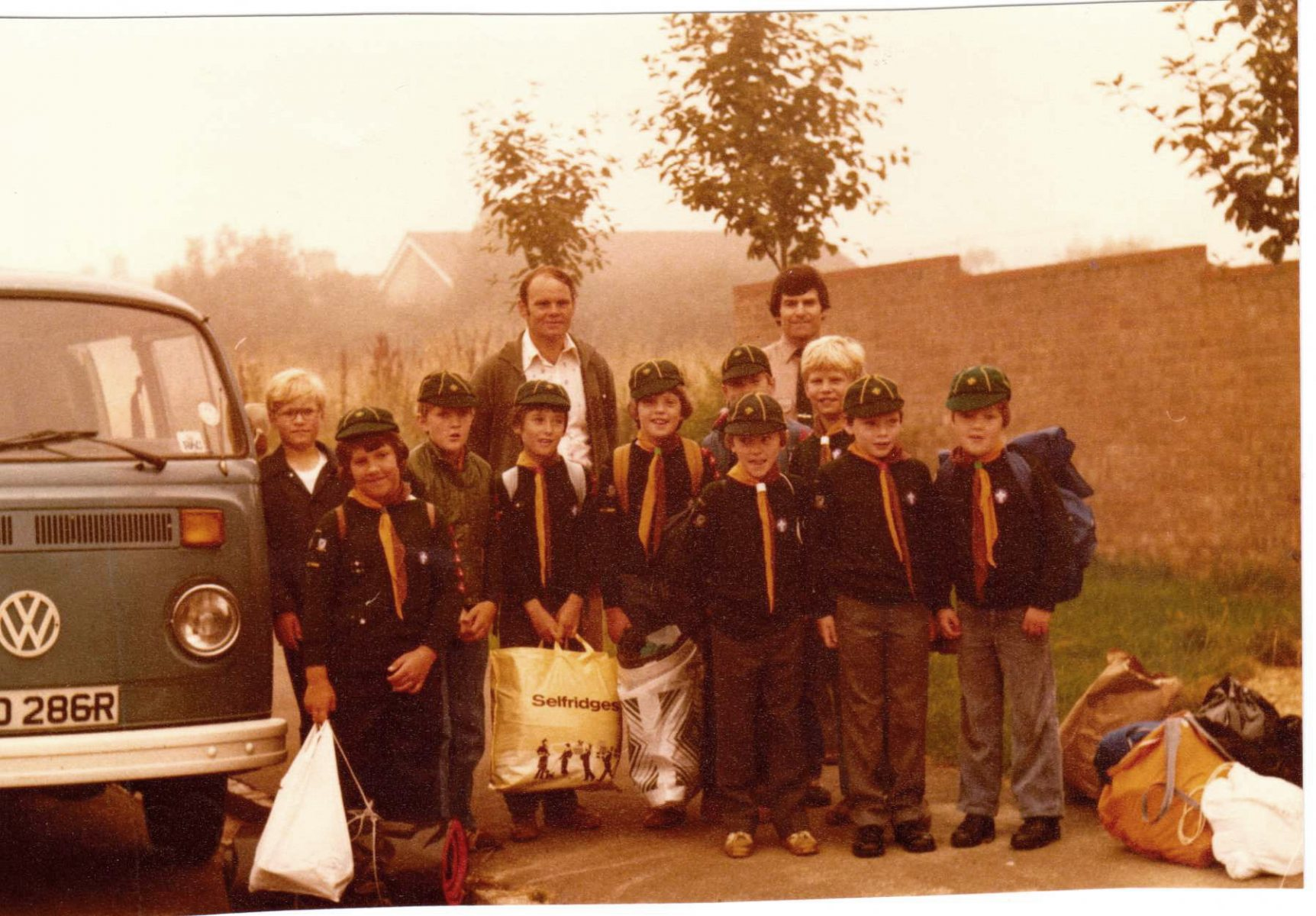 c. 1980 Bartons' Scout Group. Adults: left Lewis Yates (helper), right John Keefe (leader). Back row l to r: Kevin Benn, ?, Stephan Cox, Paul Spry, Tim Yates, Martin Benn. Front row l to r: Matthew Hansen, ?, ?, Guy ?.