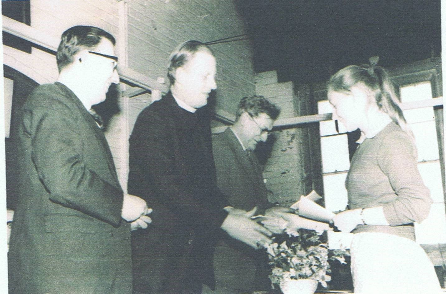 c. 1963/64. Gillian Savage receiving school prize (possibly for poetry) from Rev. Michael Hayter (rector of Steeple Aston school) in Steeple Aston school hall. Others unknown.