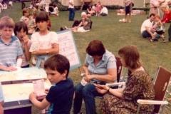 c. 1980 Middle Barton School Fete. Jamie Edbury, Tanya Southam, Tamsin Blencoe, Luke Morgan. Unknown. Teacher sitting on right is Mary Barker.  (School 2)