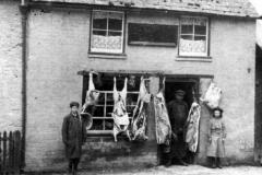 c. 1903 Thomas Grace Barrett in the butcher's shop doorway.