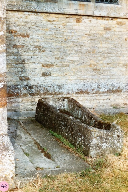 By Church porch. Mediaeval tapered coffin, believed to have come from Eynsham Abbey, which served for some years as a water trough at Whistlow Farm.