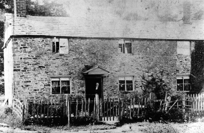 One of the cottages in the fields. Emma Luing in the doorway - demolished in 1933. The stones were carted by Charles Boffin to his yard in Worton Road (see Newman ledger) and many stones, thought to be old, were re-used.