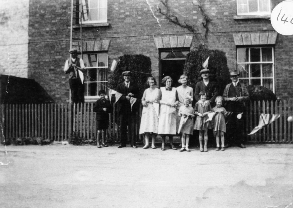 1935 George V Silver Jubilee - Putting up decorations in North Street. Mr. Walter Hazell (Cogger) on the ladder, Victor Hazell (boy). Bill Irons, Florence Hazell, Ethel Jarvis, Rose West, Tom Hazell, Sid Cox. Three girls - l to r Diana Jarvis, Violet Hazell, Barbara Jarvis.