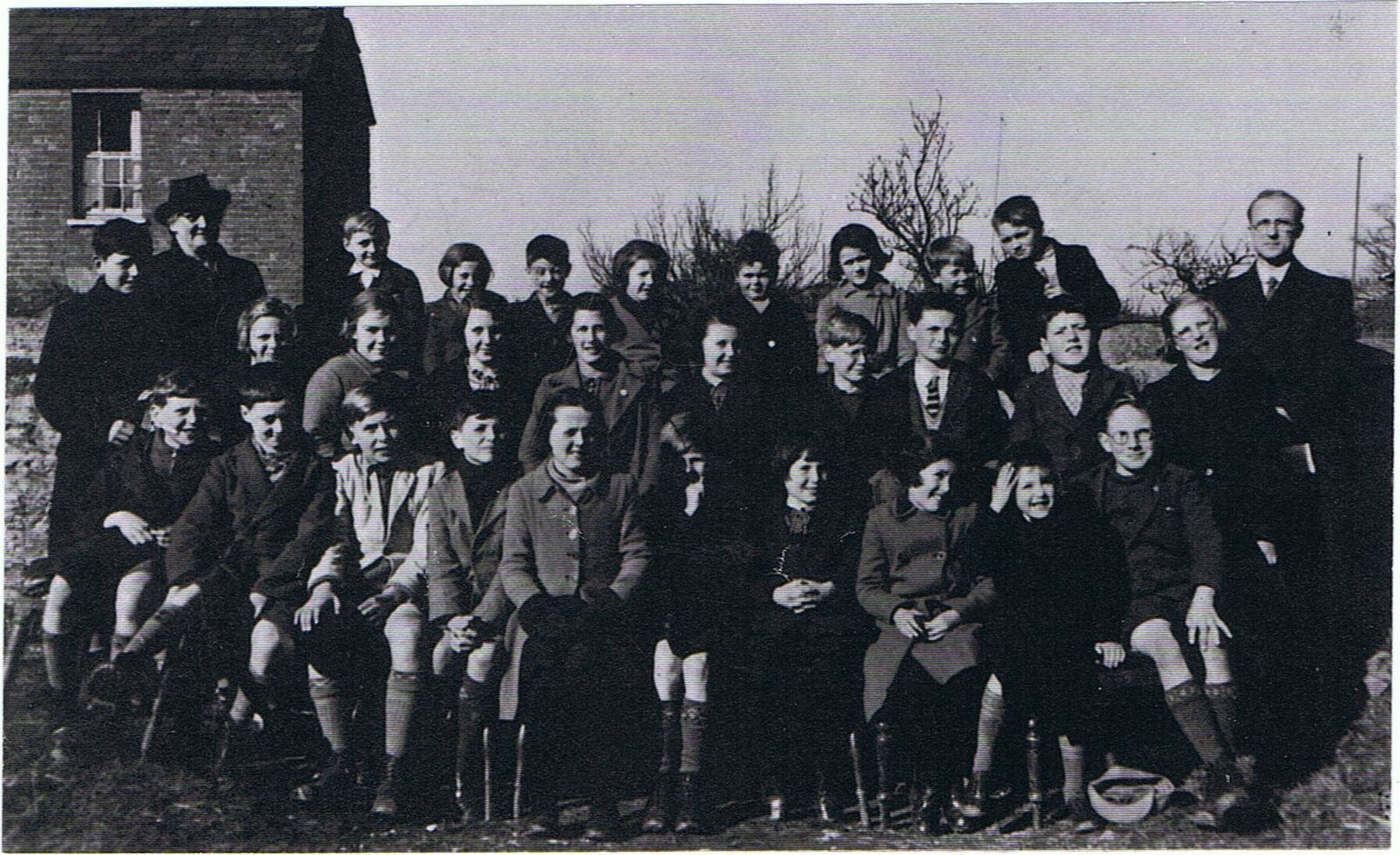 1940. Evacuees from St. Anthony's School, Forest Hill at Steeple Aston School. Mr Webster, headteacher of St. Anthony's, and his wife on the right and left of the photo. Their son is standing next to Mrs. Webster.